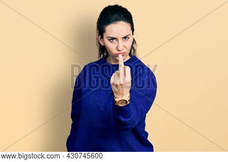 Young hispanic woman wearing casual clothes showing middle finger, impolite and rude fuck off expression