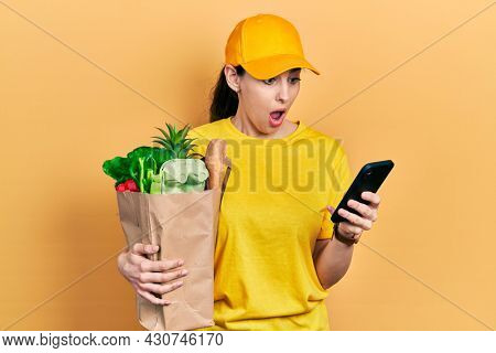 Young hispanic woman holding bag of groceries using smartphone afraid and shocked with surprise and amazed expression, fear and excited face.