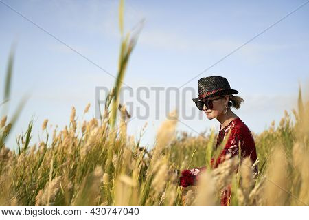 Beautiful Asian Woman With Straw Hat And Sunglasses Walking In A Reed Marsh
