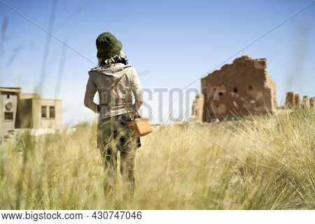Rear View Of An Asian Female Tourist Looking At Ruined Old Building