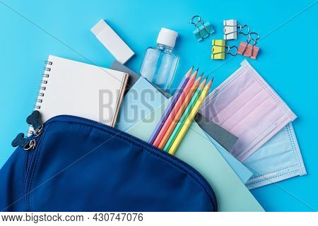 Blue Backpack With Stationery Over Blue Table Background.