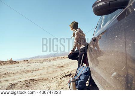 Asian Woman Traveler Leaning Against Car Looking At View In Gobi Desert
