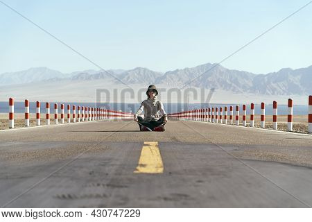Asian Woman Tourist Sitting In The Middle Of An Empty Open Road With Lake And Rolling Mountains In B