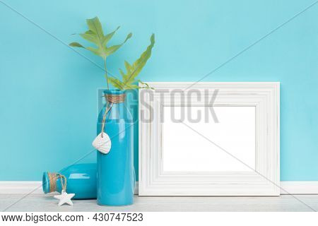 White shabby chic horizontal picture frame with two blue vases, fern leaves, turquoise wall. Poster mockup. Blank image area isolated with clipping path.