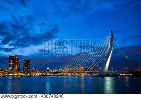 View of Erasmus Bridge (Erasmusbrug) and Rotterdam skyline cityscape illuminated at night. Rotterdam, Netherlands