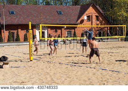 Kaliningrad Region, Russia, 10 May 2021. Men Play Beach Volleyball. Ball Players On The Beach.