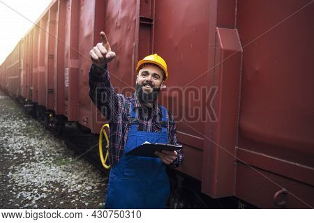 Railroad Worker Supervisor Checking Cargo And Pointing To One Of The Freight Train Cars.