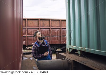Railroad Worker Supervisor Inspecting Shipping Cargo Container At Freight Train Station.