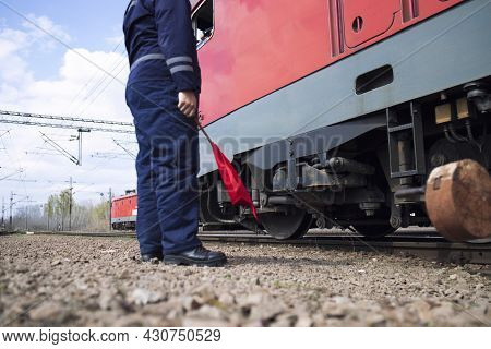 Railroad Worker Or Switchman With Red Flag Standing By The Train At The Station Ready To Give A Sign