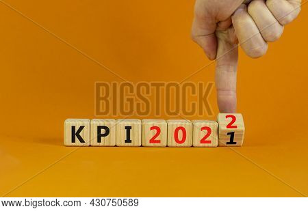 Kpi, Key Performance Indicator Symbol. Businessman Turns Wooden Cubes With Words Kpi 2021 And Kpi 20