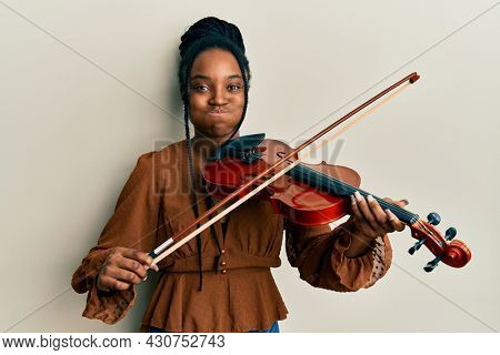 African american woman with braided hair playing violin puffing cheeks with funny face. mouth inflated with air, catching air.