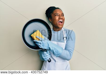 African american woman with braided hair wearing apron holding scourer washing pan angry and mad screaming frustrated and furious, shouting with anger looking up.