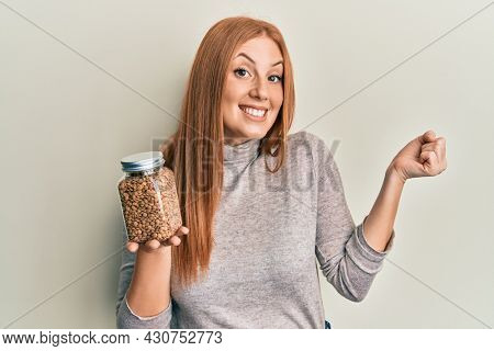 Young irish woman holding bowl with lentils screaming proud, celebrating victory and success very excited with raised arm
