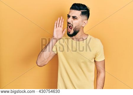 Handsome man with beard wearing casual yellow t shirt shouting and screaming loud to side with hand on mouth. communication concept.