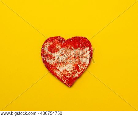 Red heart isolated on yellow background with copy space. Concept of love and feelings. Abstract symbol of passion and affection