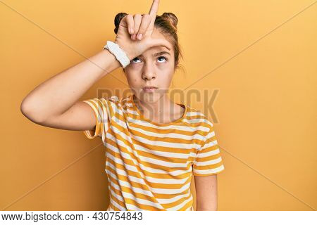 Beautiful brunette little girl wearing casual striped t shirt making fun of people with fingers on forehead doing loser gesture mocking and insulting.