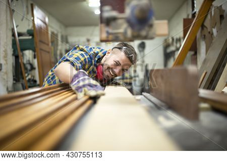 Portrait Of Experienced Carpenter Worker Cutting Wood Plank On The Machine In His Woodworking Worksh