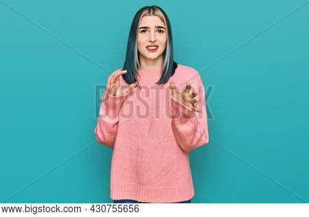 Young modern girl wearing pink wool winter sweater disgusted expression, displeased and fearful doing disgust face because aversion reaction. with hands raised