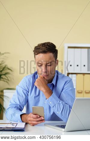 Portrait Of Pensive Young Business Executive Reading Text Message Or Article On Smartphone When Work