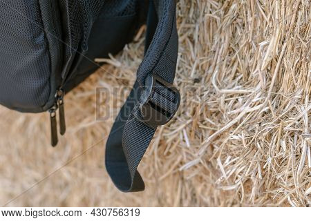 A Close-up Of The Black Strap Of The Backpack Against The Yellow Hay. Black Plastic Buckle That Adju
