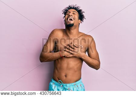 Young african american man with beard wearing swimsuit smiling with hands on chest with closed eyes and grateful gesture on face. health concept.