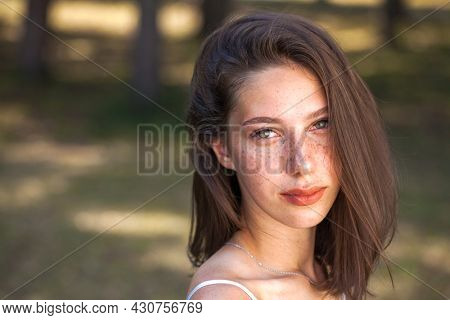 Portrait of a young beautiful brown-haired girl with freckles on her face