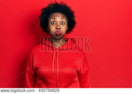 Young african american woman wearing casual sweatshirt puffing cheeks with funny face. mouth inflated with air, crazy expression.
