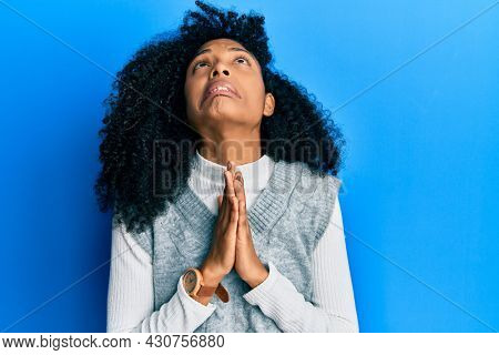 African american woman with afro hair wearing casual winter sweater begging and praying with hands together with hope expression on face very emotional and worried. begging.