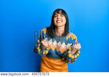 Young hispanic woman wearing casual winter sweater excited for success with arms raised and eyes closed celebrating victory smiling. winner concept.