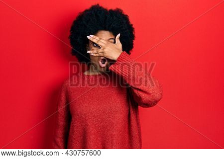 Young african american woman wearing casual clothes and glasses peeking in shock covering face and eyes with hand, looking through fingers afraid