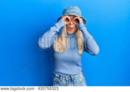 Young blonde woman wearing casual denim hat doing ok gesture like binoculars sticking tongue out, eyes looking through fingers. crazy expression.