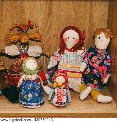 A Traditional Russian Souvenir Is A Rag Doll. A Family Of Russian Rag Dolls On A Wooden Background