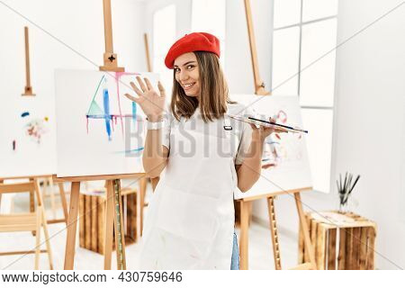 Young artist woman painting on a canvas at art studio waiving saying hello happy and smiling, friendly welcome gesture