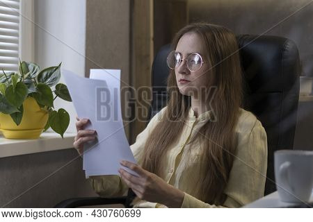 Young Woman With Glasses Sits In An Office And Reads Work Report, Agreement Or Contract