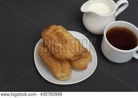 Eclairs For Tea With Milk. Profiteroles On White Saucer. Traditional French Eclairs