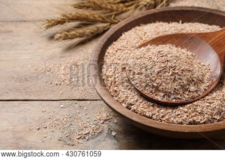 Wheat Bran And Spoon In Bowl On Wooden Table, Space For Text