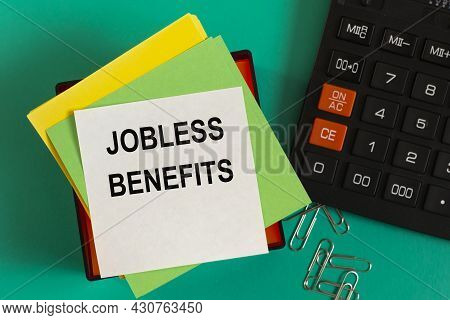Jobless Benefits - Words On Note Paper Against The Background Of A Calculator And Paper Clips. Busin