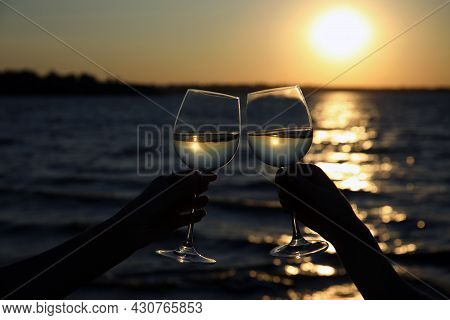 Women Clinking Glasses Of Wine Near River At Sunset, Closeup