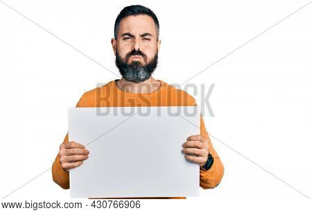 Hispanic man with beard holding blank empty banner puffing cheeks with funny face. mouth inflated with air, catching air.
