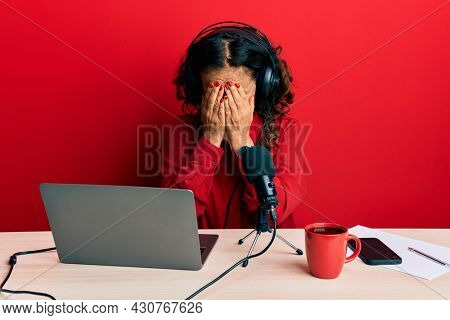 Beautiful middle age woman working at radio studio with sad expression covering face with hands while crying. depression concept.
