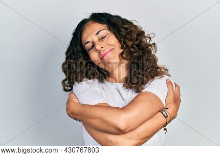 Middle age hispanic woman wearing casual white t shirt hugging oneself happy and positive, smiling confident. self love and self care