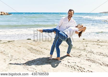 Middle age hispanic couple smiling happy dancing at the beach.