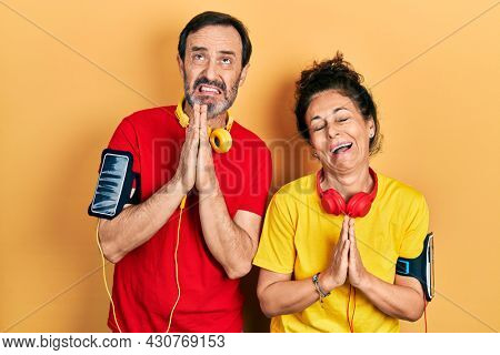 Middle age couple of hispanic woman and man wearing sportswear and arm band begging and praying with hands together with hope expression on face very emotional and worried. begging.