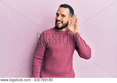 Young man with beard wearing casual winter sweater smiling with hand over ear listening and hearing to rumor or gossip. deafness concept.