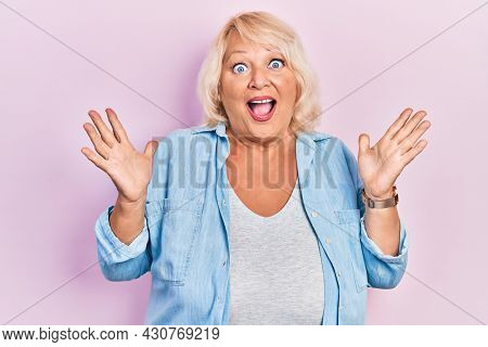 Middle age blonde woman wearing casual clothes celebrating crazy and amazed for success with arms raised and open eyes screaming excited. winner concept