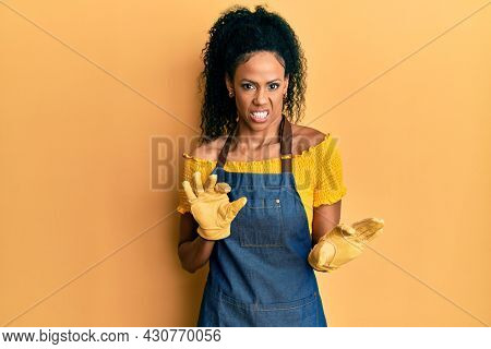 Middle age african american woman wearing professional apron disgusted expression, displeased and fearful doing disgust face because aversion reaction.