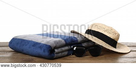 Beach Towel, Straw Hat And Sunglasses On Wooden Surface Against White Background