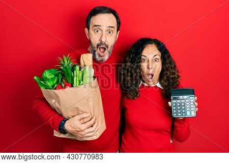 Middle age couple of hispanic woman and man holding groceries bag and calculator afraid and shocked with surprise and amazed expression, fear and excited face.