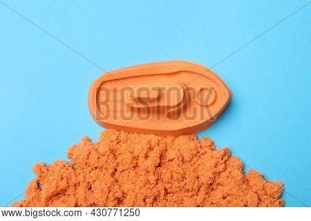 Orange Kinetic Sand On Light Blue Background, Flat Lay