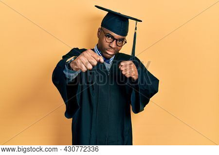 Young african american man wearing graduation cap and ceremony robe punching fist to fight, aggressive and angry attack, threat and violence